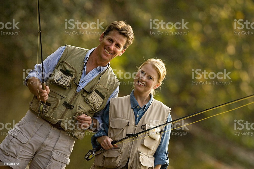 Portrait of a couple fly fishing wearing fishing vests stock photo