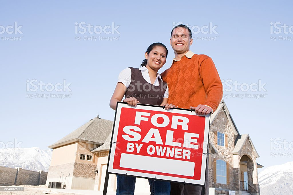 Portrait of a couple hold a for sale sign stock photo