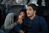 映画館で怖い映画を見ているカップルの肖像画