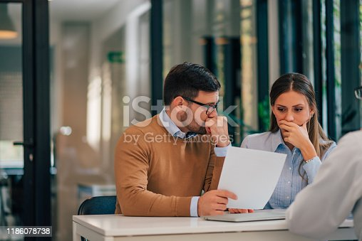 Portrait of a couple with financial problems looking at document in financial adviser's office.