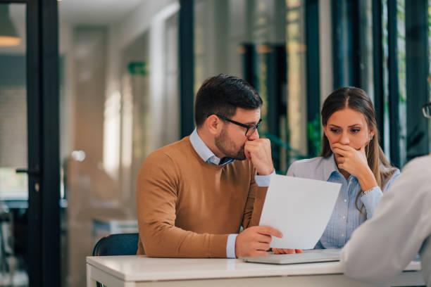 Retrato de una pareja con problemas financieros mirando documentos en la oficina del asesor financiero. - foto de stock