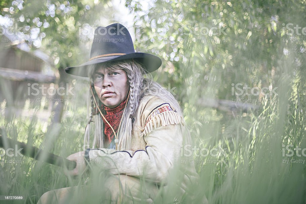 Portrait of a cowboy hiding behind some grass royalty-free stock photo