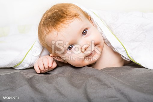 149051793 istock photo Portrait of a crawling baby on the bed in her room 850942724