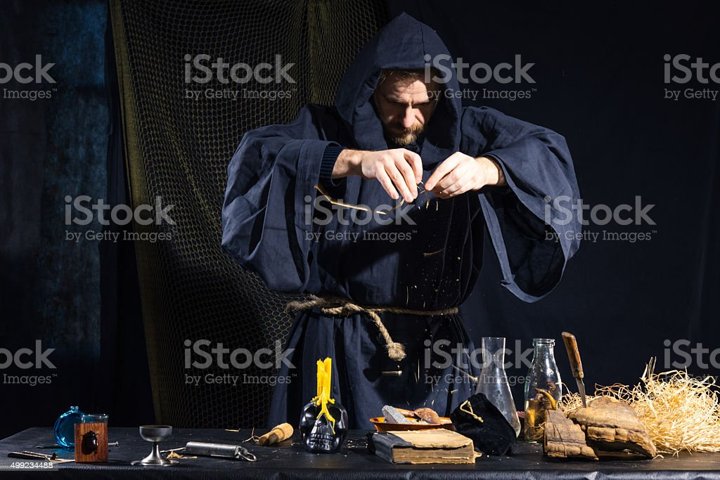Portrait of a crazy medieval scientist working in his laboratory. stock photo