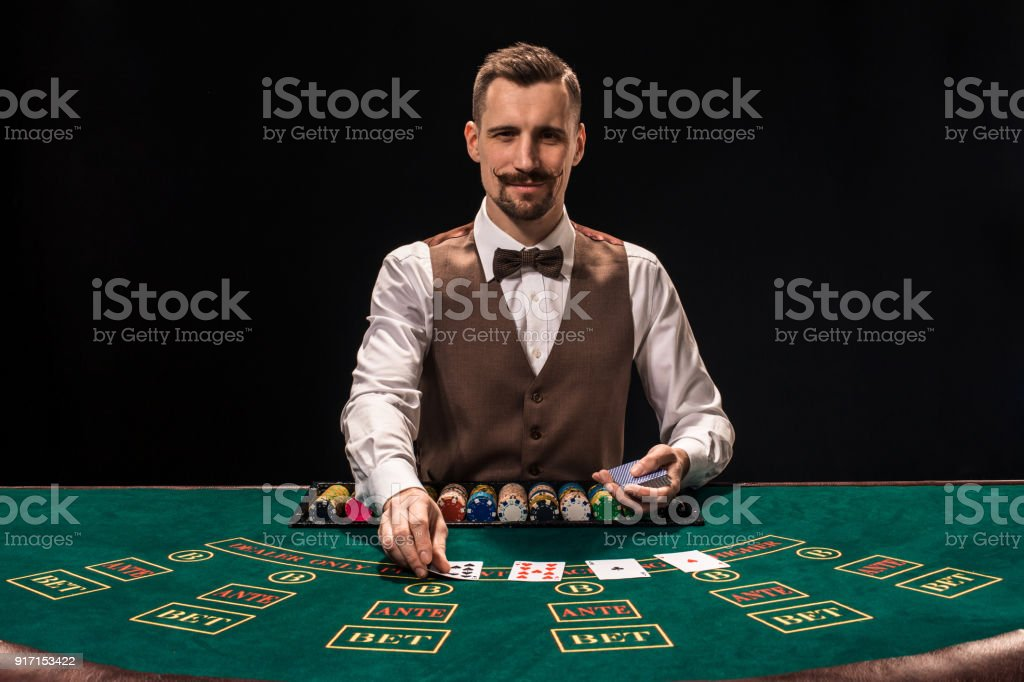 Portrait of a croupier is holding playing cards, gambling chips on table. Black background stock photo