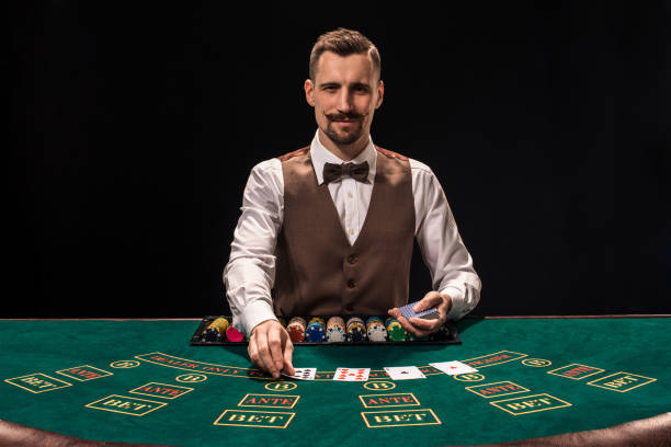 porträtt av en croupier håller spelkort, gambling chips på bordet. svart bakgrund - black jack bildbanksfoton och bilder