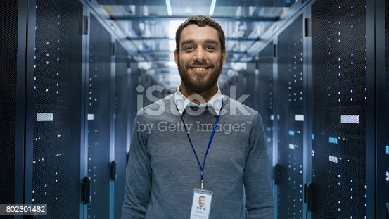 802303638istockphoto Portrait of a Curios, Positive and Smiling IT Engineer Standing in the Middle of a Large Data Center Server Room. 802301462