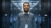 istock Portrait of a Curios, Positive and Smiling IT Engineer Standing in the Middle of a Large Data Center Server Room. 802301462