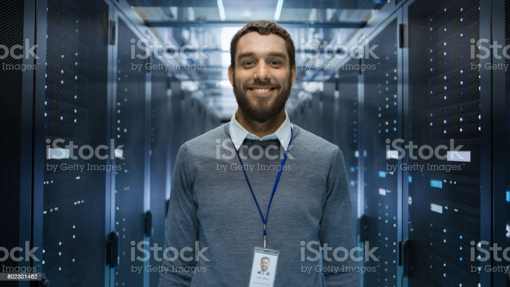 Portrait of a Curios, Positive and Smiling IT Engineer Standing in the Middle of a Large Data Center Server Room. stock photo