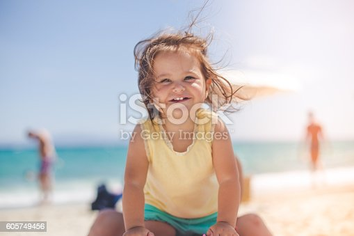 istock portrait of a cute baby girl on the beach 605749456