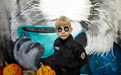 istock Portrait of a cute funny kid in police costume posing on the street 1282992104