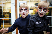 istock Portrait of a cute funny kids in Halloween costumes with frightening expression posing on the street 1282992108