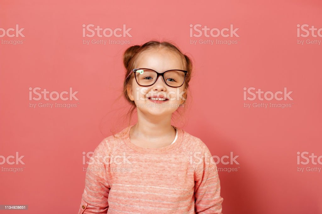 fba9cd5c55 Portrait of a cute little 6 year old girl wearing eyeglasses on a pink  background royalty