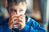 Portrait of a cute little boy drinking a glass of water. The boy is 8 years old.\nNikon D850