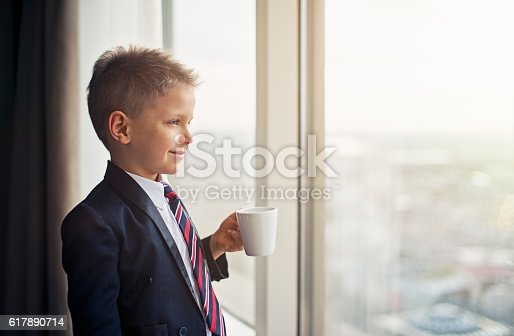 Portrait of a smiling cute blonde boy wearing a suit and a tie. The boys is aged 6 and he's looking at the city holding a cup of coffee or chocolate. The boy is dreaming of becoming a businessman.