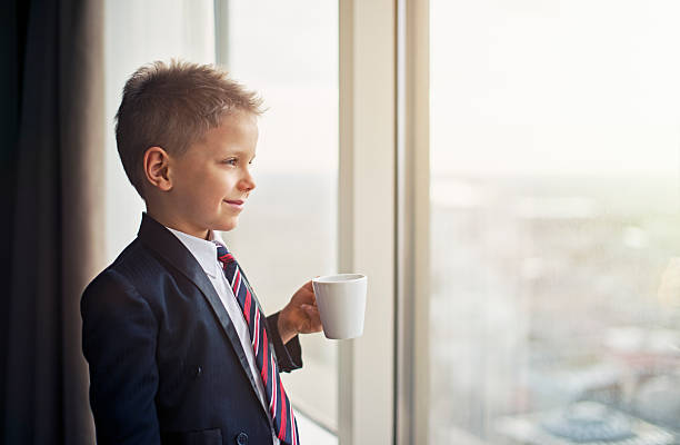 portrait of a cute little business man - boy looking out window stock pictures, royalty-free photos & images