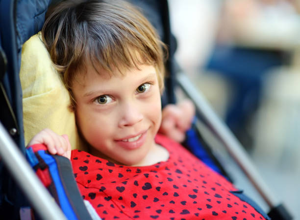 Portrait of a cute little disabled girl in a wheelchair. Child cerebral palsy. Inclusion. stock photo