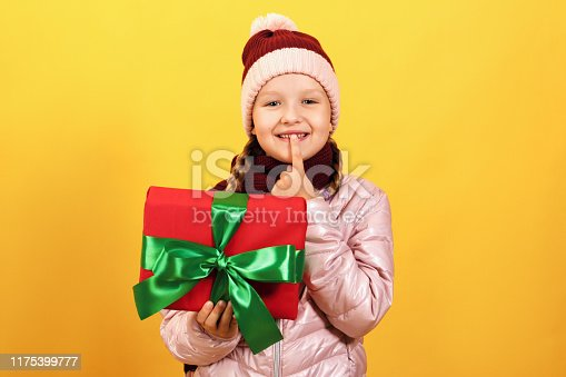 Portrait of a cute little girl in a jacket, scarf and hat on a yellow background. The child holds a box with a gift and shows a sign shh.