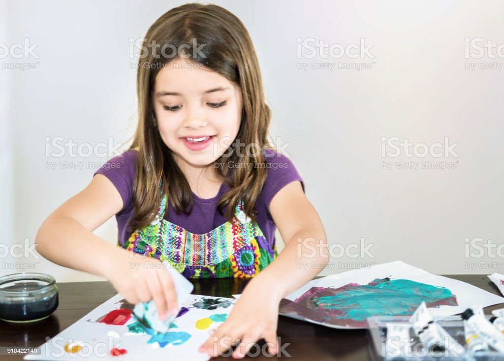 Portrait of a cute smiling girl painting a picture stock photo