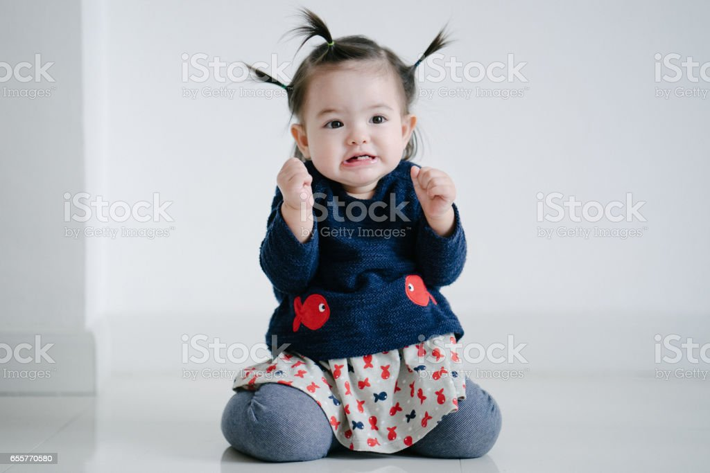 Portrait of a cute toddler girl grimacing stock photo