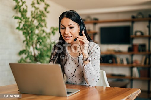 Portrait of a cute woman with headset and laptop at home office.