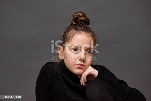 Portrait of a cute young girl posing in a studio with a hair bun and hand on her chin.