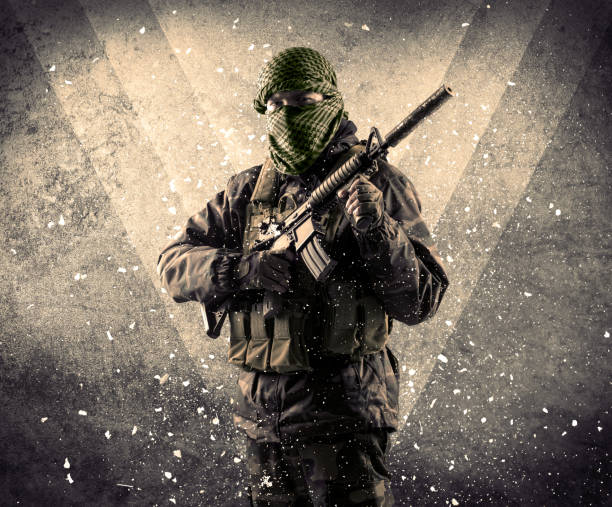 Portrait of a dangerous masked armed soldier with grungy background stock photo