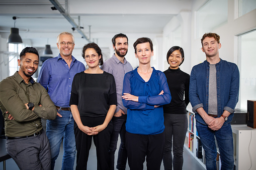 Portrait of a diverse business team looking at camera. Multi-ethnic group of business people standing in office.