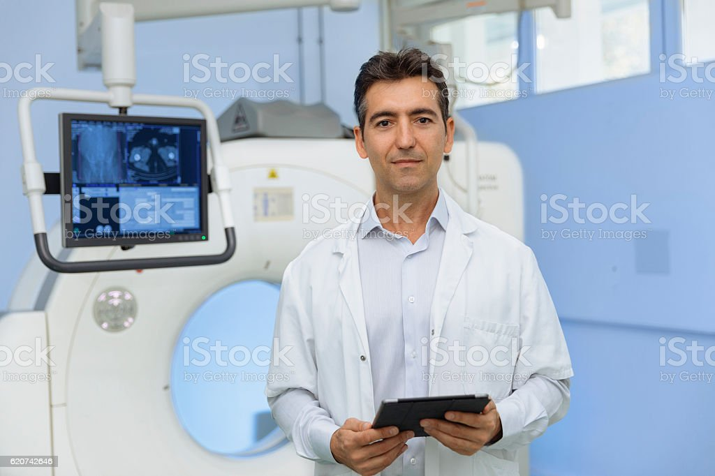 Portrait of a doctor front of a scanner stock photo