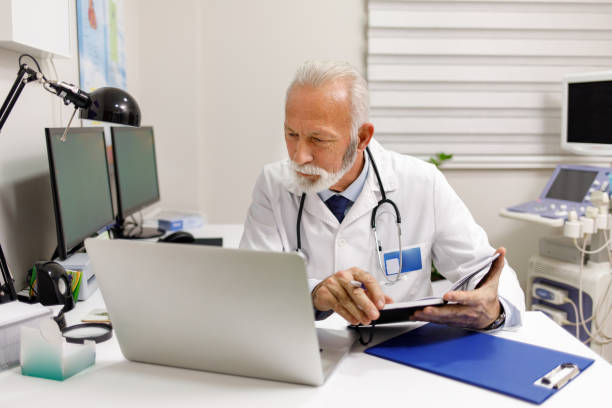 Portrait of a doctor looking at medical charts on his laptop stock photo