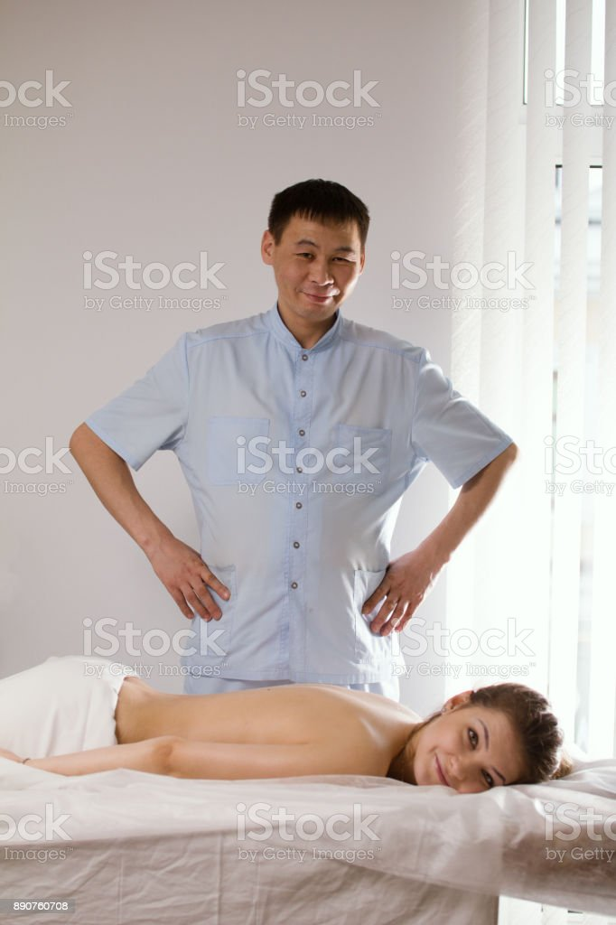 Portrait of a doctor massagist and patient - young woman lying on massage table - before SPA procedure stock photo