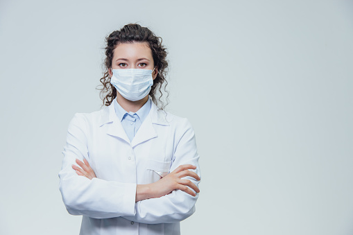 Portrait of a doctor of a beautiful and young woman. In a white robe there is a gray background. Dressed in a white face mask. Put your hand on your arm.