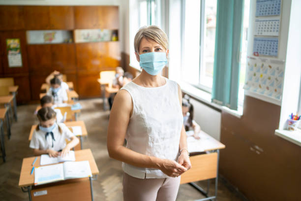 COVID-19. Portrait of a elementary teacher wearing protective face mask stock photo