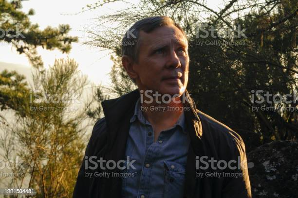 Photo of A portrait of a european belarusian man 50+ years old who is enjoying the sunset light in the forest