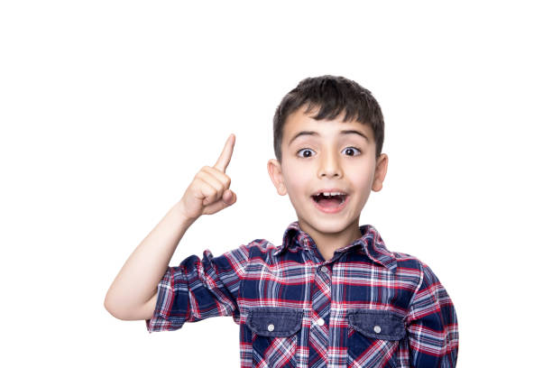 Portrait of a excited child pointing over white background Portrait of a excited child pointing over white background. Horizontal composition. Studio shot. 6 7 years stock pictures, royalty-free photos & images