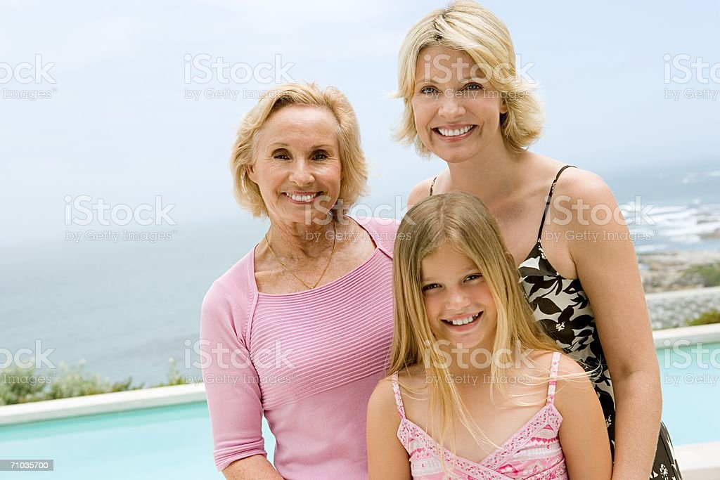 Portrait of a family by a swimming pool stock photo