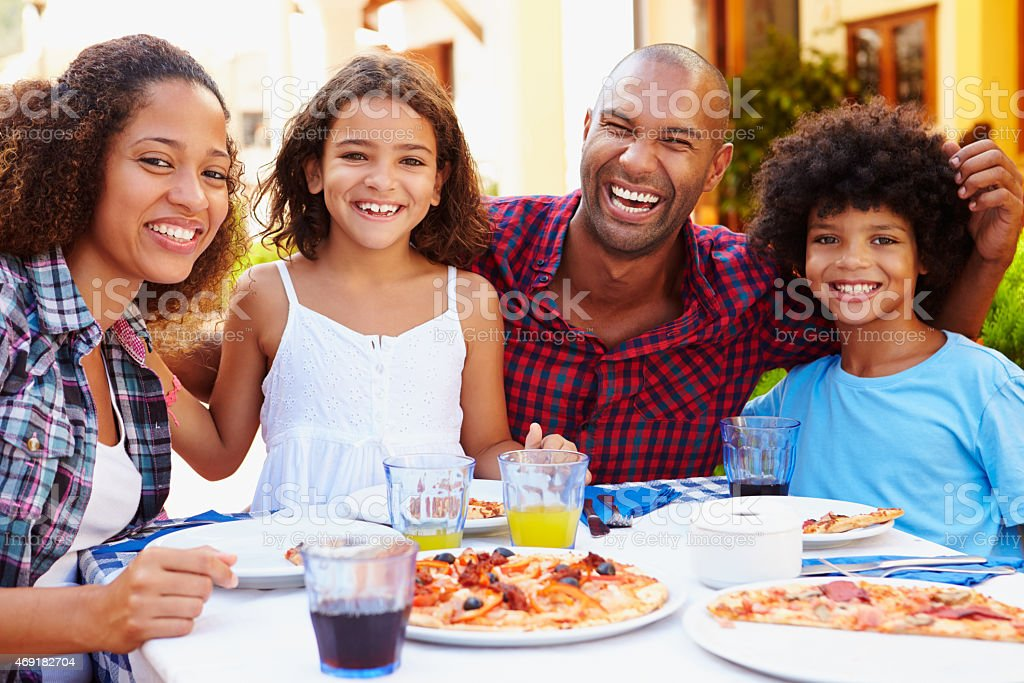 Portrait of a family having pizza outdoor at restaurant stock photo