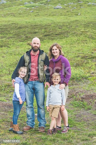 Portrait of two parents and their children on an Alaskan mountain midway through a hike. They are standing and embracing each other and are on a hillside covered with grass and rocks.
