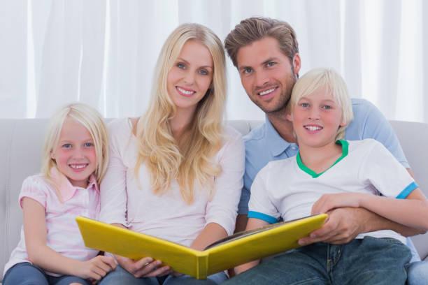 porträt einer familie mit einem märchenbuch - kurzgeschichten stock-fotos und bilder
