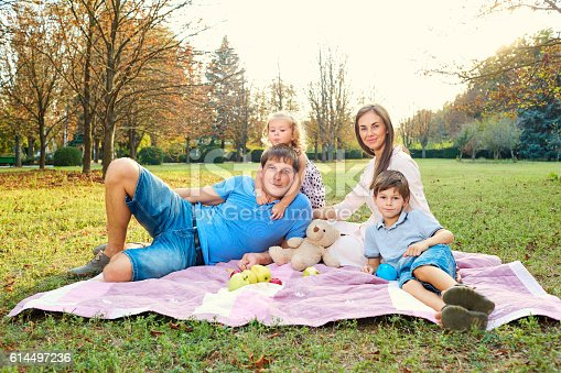 588959064istockphoto Portrait of a family in the park lying  grass relaxing 614497236