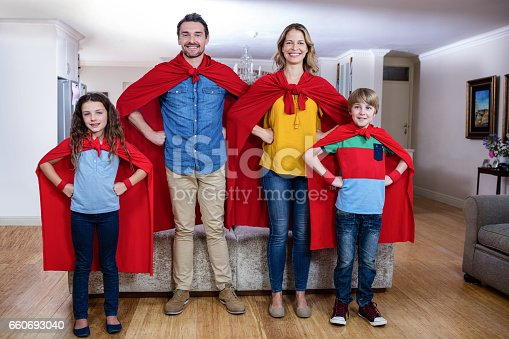 516318379istockphoto Portrait of a family pretending to be superhero in living room 660693040