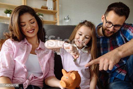 Portrait of a family saving money in piggybank