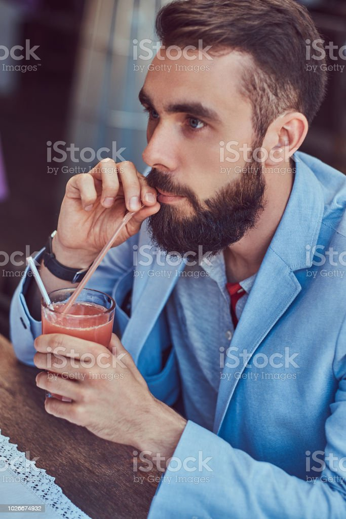 Portrait of a fashionable bearded male with a stylish haircut, drinks a glass of a juice, sitting in a cafe outdoors. stock photo