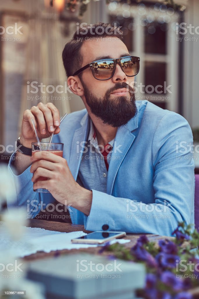 Portrait of a fashionable bearded male with a stylish haircut, holds a glass of a cappuccino, sitting in a cafe outdoors. stock photo