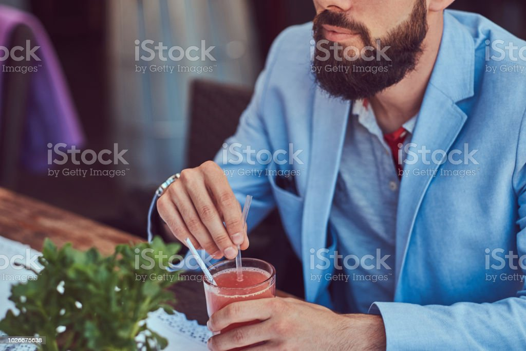 Portrait of a fashionable bearded male with a stylish haircut, holds a glass of a juice, sitting in a cafe outdoors. stock photo