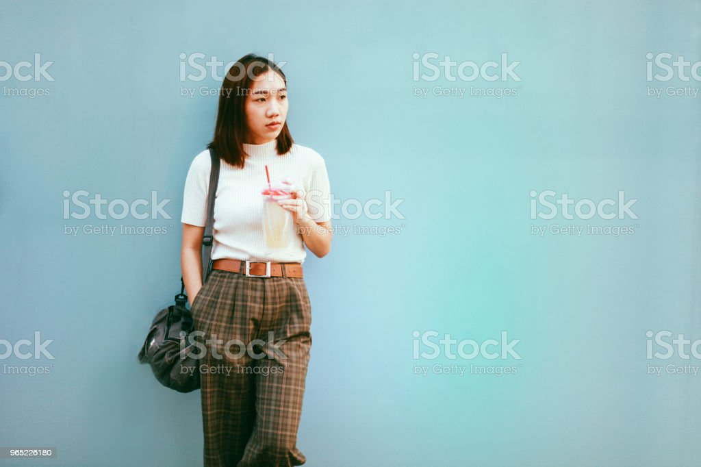 Portrait of a fashionable young Asian girl leaning on a turquoise wall zbiór zdjęć royalty-free