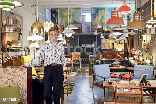 Portrait of a female business owner standing in her furniture store.
