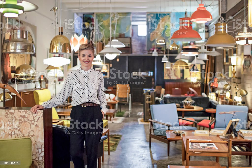 Portrait of a female business owner standing in her furniture store stock photo