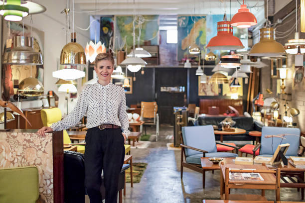 portrait of a female business owner standing in her furniture store - furniture shopping stock photos and pictures