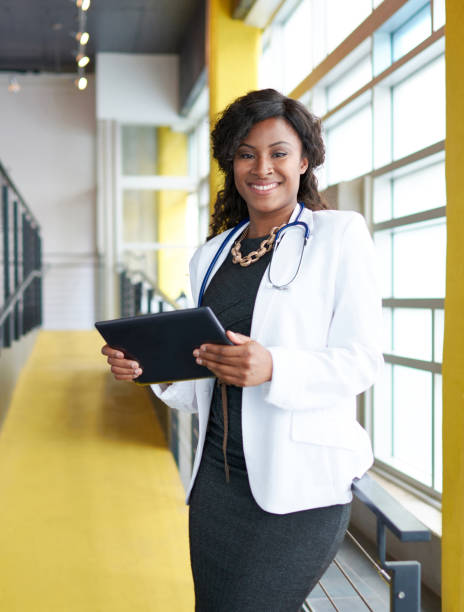 Portrait of a female doctor holding her patient chart on digital tablet in bright modern hospital stock photo